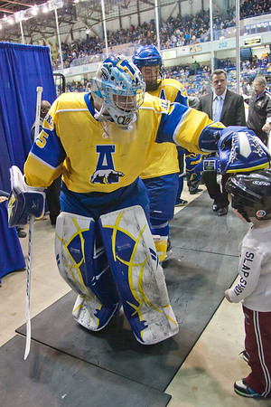 Goalie Scott Greenham stops on the way to the locker room between periods to interact with a young fan in the Carlson Center.  Filename: ATH-12-3304-113.jpg