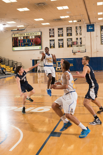 """Junior forward Bangaly Kaba rifles a pass inside to Travante Williams during the Nanooks' 92-69 win over Concordia University Feb. 20 in the Patty Gym.  <div class=""""ss-paypal-button"""">Filename: ATH-16-4810-58.jpg</div><div class=""""ss-paypal-button-end""""></div>"""