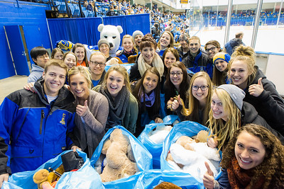 Student athletes pose for a photograph after collecting plush toys on the ice during the 3rd Annual Teddy Bear Toss at a hockey game in Carlson Center. The Student-Athlete Advisory Committee sponsored the event that collects toys for families during the holiday season.  Filename: ATH-13-4011-76.jpg