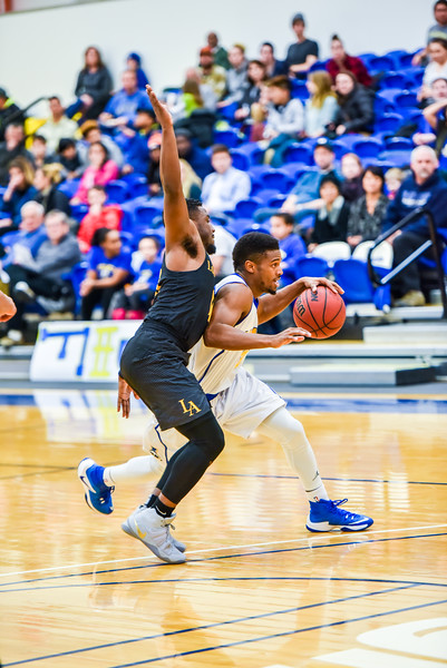 """A UAF player narrowly dribbles around an opponent from Cal State LA during the Nanooks' game on Nov. 21 in the Patty Gym.  <div class=""""ss-paypal-button"""">Filename: ATH-16-5072-27.jpg</div><div class=""""ss-paypal-button-end""""></div>"""