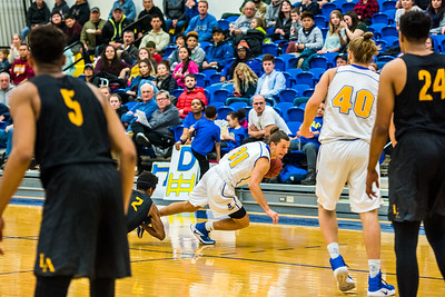 A player from Cal State LA grabs Brandon Davis' leg and pulls him down during the Nanooks' game on Nov. 21 in the Patty Gym.  Filename: ATH-16-5072-61.jpg
