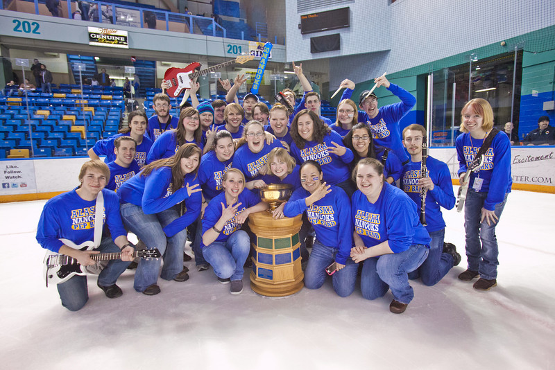 """The UAF Pep Band huddles around the Governor's Cup on the ice in the Carlson Center after  helping the Nanooks win the coveted trophy for the third time in the last four years with a thrilling victory over the UAA Seawolves.  <div class=""""ss-paypal-button"""">Filename: ATH-12-3304-368.jpg</div><div class=""""ss-paypal-button-end"""" style=""""""""></div>"""