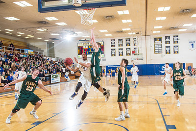 Junior Joe Slocum drives the lane for a layup late in the Nanooks' game against the UAA Seawolves in the Patty Gym. Slocum's goal helped the Nanooks overcome a 13-point second-half deficit and defeat the Seawolves on a buzzer-beating bucket by Andrew Kelly.  Filename: ATH-14-4097-7.jpg