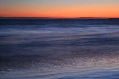 Abstract of ocean and sky at dusk with deep blue and orange gradient.