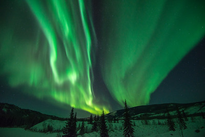 Northern Lights illuminate the landscape with a green glow during a moonless night