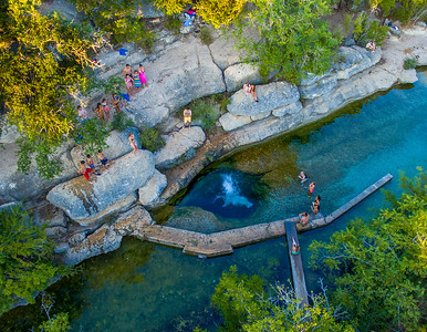 Jumping into Jacob's Well Spring. The Well is in Cypress Creek near Wimberley.