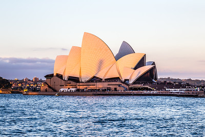 The Sydney Opera House at sunset. As the sun was in the process of going down it got obscured by clouds. It finally came back but by then something was casting a shadow. Based upon the sunset direction given by The Photographer's Ephemeris and a photo I took yesterday of The Rocks from the east side of Circular Quay, the shadow is being cast by a historic smokestack in The Rocks. I'm not sure what the significance of the smokestack is - Google has failed me.