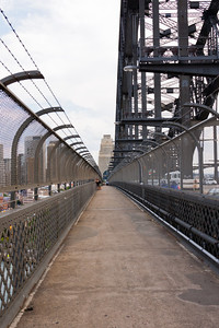 The pedestrian walkway of the Sydney Harbour Bridge.  There is a gap below the chain link fence to take pictures from.