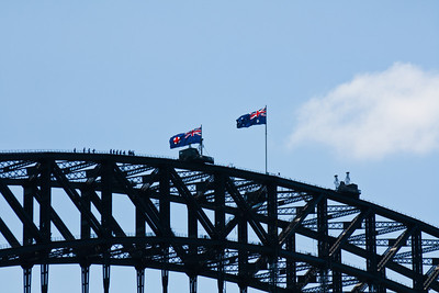 The top of the Sydney Harbour Bridge.  To the left of the flags is a group of people doing the Sydney Bridge Climb.  People doing the climb are visible at all hours of the day and at sunset.