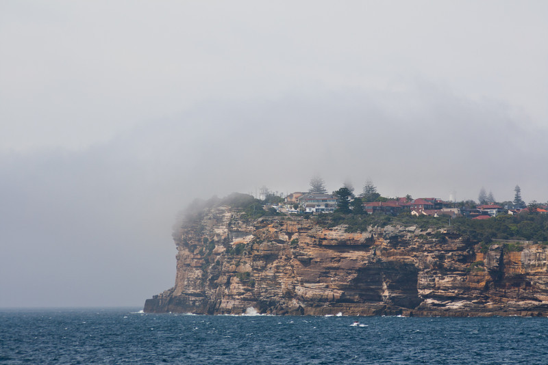 Fog shrouded cliff near where the harbour opens out to the sea