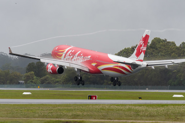MMPI_20200208_MMPI0063_0036 - AirAsia X Airbus A330-343 9M-XXT (Xcintillating PhoeniX Livery) as flight D7200 touches down at Gold Coast Airport (YBCG) ex Kuala Lumpur (WMKK) trailing wingtip vortices.