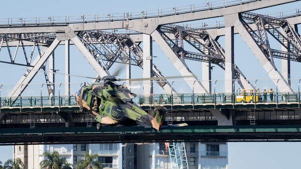 MMPI_20210923_MMPI0078_0020 - Australian Army NHIndustries MRH-90 Taipan A40-027 pulls up beside the Story Bridge during its flying display practice for Brisbane Festival Riverfire 2021. A pair of workers watch on from the bridge deck.