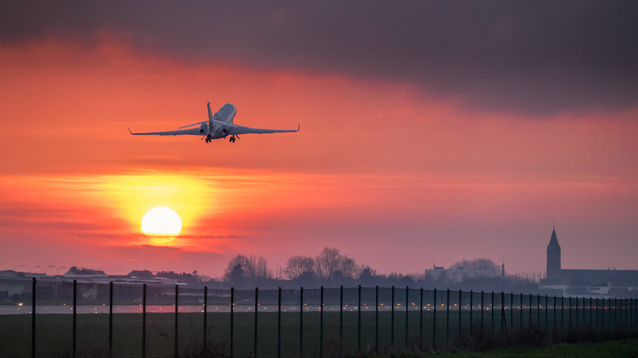 Falcon 7X flying into the sunset