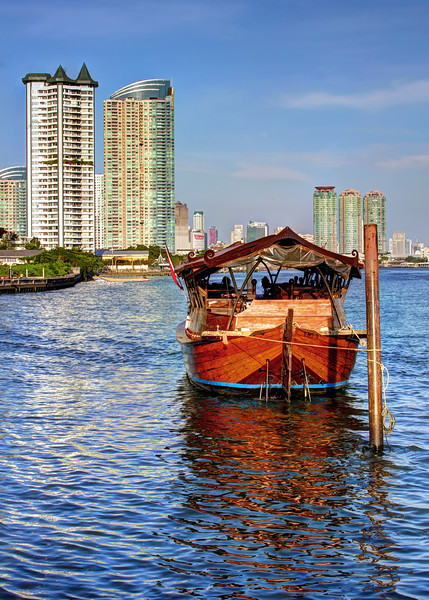 Reflection of the old against the backdrop of the new  Rice Barge on the Chao Phraya River  Bangkok