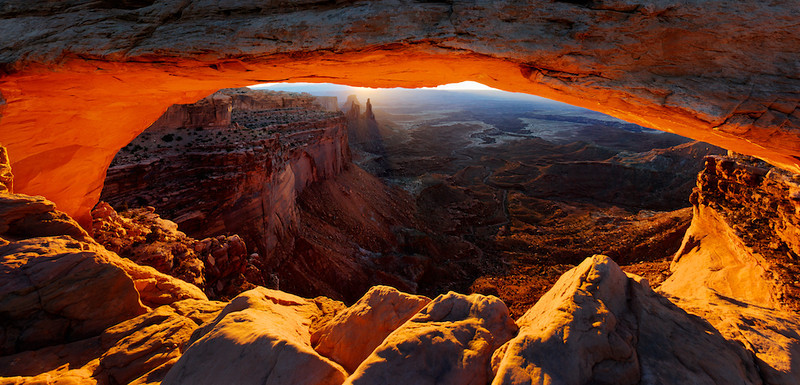 """BEHIND THE IMAGE:  MESA ARCH AT SUNRISE  Mesa Arch at Sunrise - Canyonlands National Park, Utah, File# 0505098  <a href=""""http://www.tom-hill.biz/Galleries/Scenics/Utah/20957775_CZGg5B#!i=1665217427&k=gF8TKvQ&lb=1&s=A"""">  Link To Original Image </a>  If you've ever been to Canyonlands National Park, you've likely been to this location.  One of the iconic locations in the southwestern United States, Mesa Arch has become one of the most recognizable images of this area.  One of the deceiving features of this arch and with photography in general is you really don't get a good reference for size and proximity.  The opening of Mesa Arch is about 20 feet.  From top to bottom, the height is about five feet.  What you don't really get is the drop off just beyond the foreground rocks is more than a thousand feet!  It's pretty amazing.  You can tell there are little traces of snow in the valley.  It sure was cold this morning.  Even though spring was in full-swing at lower elevations, this area was still clinging to the last bits of the previous winter.  As a result, the wind went through you like knife blades.  While the ambient temp was a moderate 32 deg F, the blowing wind would've been impossible if I wasn't wearing wind blocking clothing.  So, the environmental conditions were a challenge.  No biggy.  The real challenge was getting the entire orifice of the arch without shooting one of the other many photographers there.  And, to capture the full range and detail of the morning light--conquer the dynamic range problem of the scene.  The best way to get away from the other photographers in this situation was to get as close to the arch as possible without being in their way.  Fortunately or unfortunately, this dictated that I couldn't get the top part of the arch and my composition was a bit out of control.  The problem with being so close to the arch was two-fold.  First challenge was getting a wide enough field of view to get as much as I could.  The second challenge was """