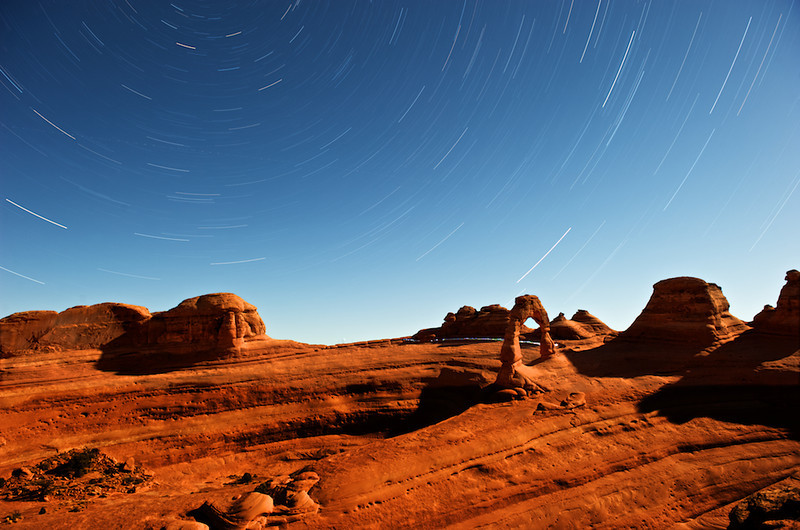 """BEHIND THE IMAGE:  DELICATE ARCH AND STAR TRAILS  Delicate Arch & Star Trails - Arches National Park, Utah, File# 0907779  <a href=""""http://www.tom-hill.biz/Galleries/Scenics/Utah/20957775_CZGg5B#!i=1665219474&k=hQpWmnf&lb=1&s=A"""">  Link To Original Image </a>  Last fall I took a trip to Utah with stops in Moab and Arches National Park. One of the iconic subjects of the park, perhaps of even picturesque Utah, is Delicate Arch. At the end of a moderately difficult trail, you can find the arch most beautiful at sunset when the warm light really makes the arch glow. The most common way the arch is viewed is from the north just next to it.   A less common view of the arch is from the south, from the vantage point illustrated here. I guess it's even more difficult to reach this point. And, it's not marked at all with probably makes the location less assessable and therefore the arch less commonly captured from this angle.   I like this view for just these reasons. It's less common. Even then, the day I shot this image, I was joined by six or seven of my """"best stranger friends"""" from around the world. I wonder if they were there because I was so prominately positioned across the way. Without me being there, maybe my """"best friends"""" wouldn't have been motived to explore their way to that point. I don't know.  Even though there were only six or seven folks there and the more common location had literally dozens and dozens of tourists, I knew I could create an even more atypical image by simply capturing start trails.   I won't completely describe the technical steps of the technique here. That's meant for another article elsewhere in the website. For here, I'll talk about what I had to do onsite to make this image.  Absolutely important to the success of this image or any like it is you have to project yourself later in the evening to anticipate what the scene will look after the sun is down. What I did was get to my shooting location about an hour prior to sunset. I imagined h"""