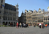 "Across the ""Grand Place"" (French) or ""Market Square"" (Dutch) - to the shaded northern corner of the Stadhuis (Town Hall) - and the mostly sunlit guild halls (places where an association of craftsmen in a particular trade assembled).  The, shaded Le Renard (with Saint Nicholas atop), the partially sunlit ""The Horn"" (guild hall of the boatmen), the first sunlit guild hall (with the phoenix on top of the gable ), is the ""De Wolvin"" (the She-Wolf) - at that time it was a wooden building - it was bought by the Archers Guild, and after a fire in 1690, the guil hall was rebuild in stone - in the tympanum you see, Apollo piercing the snake ""Pyton"""
