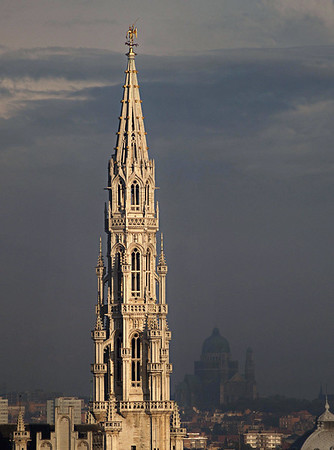 Late evening sunlight upon the 16 ft. (5 m) high gilt metal statue of the archangel Michael, patron saint of Brussels, slaying the devil (evil), atop the spire of the Stadhuis (Town Hall) - with the Koekelberg Basilica (rising 540 ft. - 165 m), along the distal horizon - Brussels