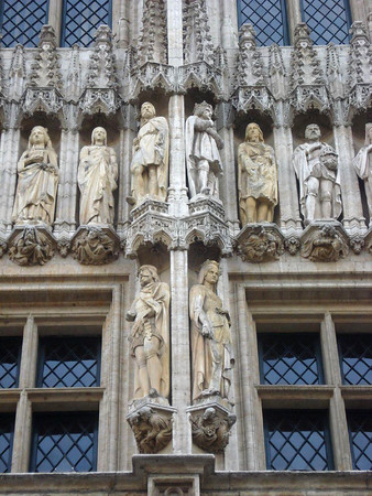 """Along the facade of the Town Hall (Stadhuis) - displaying statues of nobles (dukes and dutchesses) and saints of """"The Duchy of Brabant"""" - a duchy (territory) of the Holy Roman Empire between 1183–1648 covering parts of the Netherlands and Belgium, ruled over by the Dukes of Brabant - Brussels."""