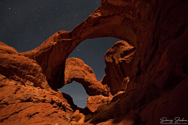 Double Arch at Arches National Park, as seen by moonlight with the stars showing brightly overhead.