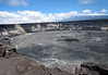 Halema'uma'u Crater - around 270 ft. (82 m) deep - with an active fissure releasing sulfurous gas and particles along the crater wall (L) - and the slope of Mauna Loa (a dormant volcano) along the distal horizon, and among the clouds - Hawaii Volcanoes National Park