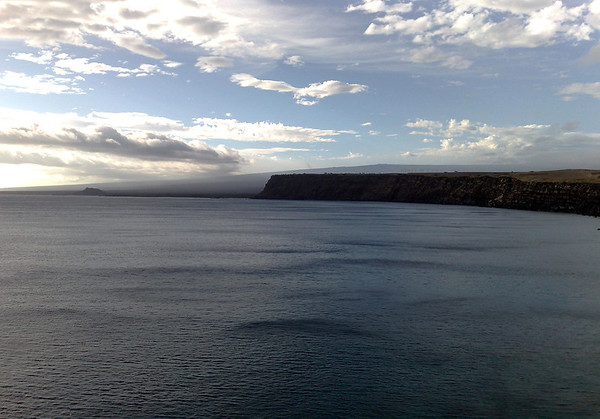 Afternoon clouds casting a shadow across the Pacific Ocean from South Point - to Pali o Kulani Point - and to the distal 240 ft. (73 m) tall Pu'uhou (New Hill) - with the southwestern slope of the Mauna Loa Volcano along the horizon - Kaʻū district