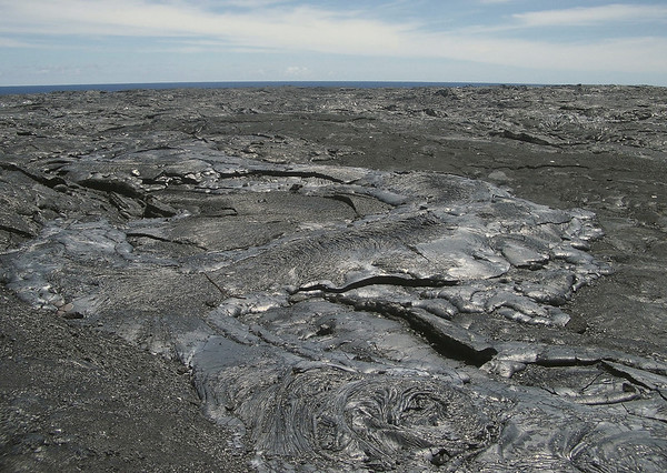 Across the newly solidified lava - Pahoehoe (a basaltic lava, that has a smooth, billowy, and undulating surface) - to the Pacific Ocean - Hawaii Volcanoes National Park