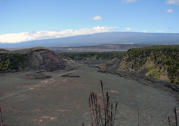 Kiluea Iki (Little Kiluea) Crater - from the northeast rim of the circular crater, down to the trail across the crater floor and into the gap, adjacent to Pu'u Pua'i cinder cone, where the lava lake eventually ruptured - beyond the gap is the vegetated northeastern rim of the Kilauea Caldera - and the northern end of the Halema'uma'u Crater - in the Hawaii Volcanoes National Park - and the distal slope of Mauna Loa Volcano beyond