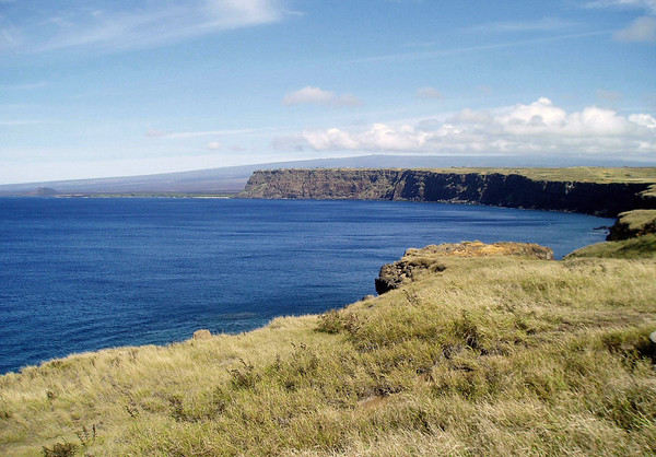 From from the grass plateau of South Point - across the Pacific waters to, Pali o Kulani Point, rising around 300 ft. (91 m) - with Pu'uhou (New Hill), peaking 240 ft. (73 m) tall, along the distal shoreline - and the southwestern flank of Mauna Loa Volcano along the horizon - Kaʻū district