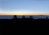 Sunset over the Subaru, Keck and NASA Observatories - atop the Mauna Kea Volcano - with the summit of Haleakala Volcano, rising to 10,023 ft. (3,055 m) above the cloud blanket on the island of Maui