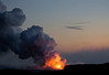 Pu'u O'o lava glow at dusk - with the steam plume rising from the shore of the Pacific Ocean - Hawaii Volcanoes National Park