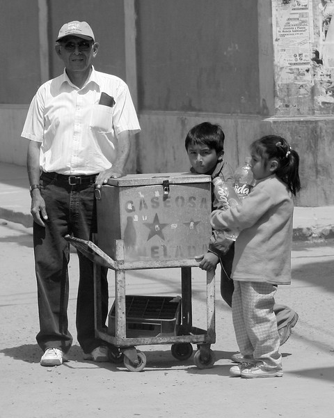 Elderly gentleman and children selling beverages along road in Ica, Peru