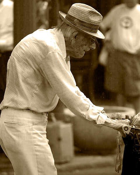 older gentleman pushing grocery cart in rain downtown New Orleans