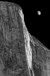Moon rising behind El Capitan granite rock formation in Yosemite, California