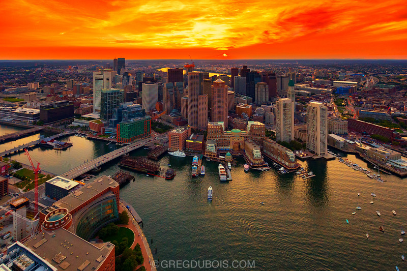 Dipping Sun and Fiery Sunset over Boston Skyline and Waterfront from the Sky
