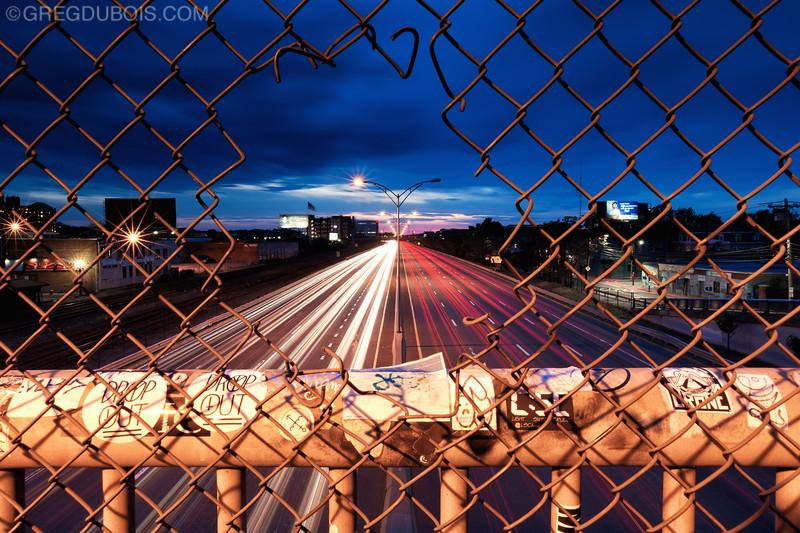 Mass Pike Light Trails through Chain Link, Dusk over Allston Neighborhood of Boston
