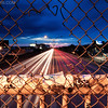 Mass Pike Light Trails through Chain Link Hole and Railing, Stormy Dusk over Allston Neighborhood Boston