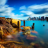 Carlton's Wharf East Boston during Day with Decayed Pilings and Rocky Shoreline, Boston Skyline over Boston Harbor with Cloud Movement