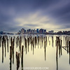 Lost Pier of Maverick Landing in East Boston with Decayed Pilings and Boston Skyline under Stormy Sky