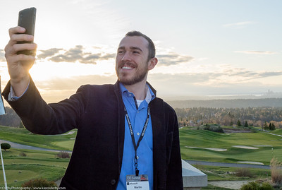Selfie! with the Seattle skyline in the background.  A Microsoft CIO Summit guest enjoys sunset at The Golf Club at Newcastle.