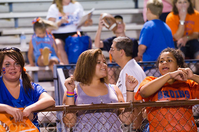 Fans and Volunteers at the game working Hard and cheering their school on.
