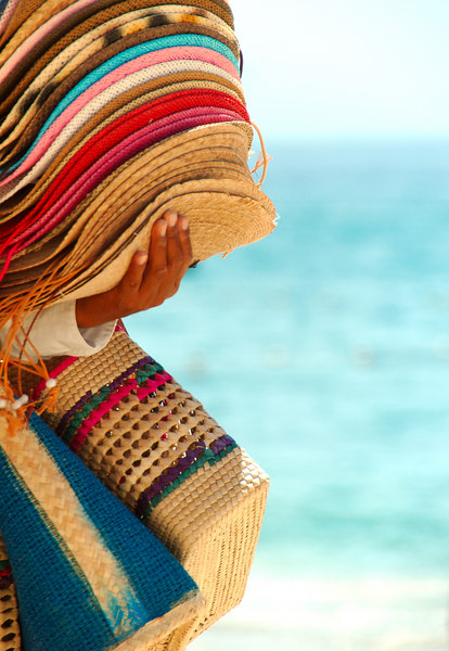 Stack of Straw hats and several straw bags on the arm of a beach vendor.  There is blue ocean and pale blue sky in the blurred background.