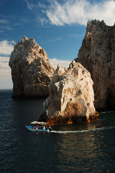 Tour boat is circling a rock formation.  The sky is a deep blue with wispy clouds.  Los Arcos, Cabo San Lucas, Mexico