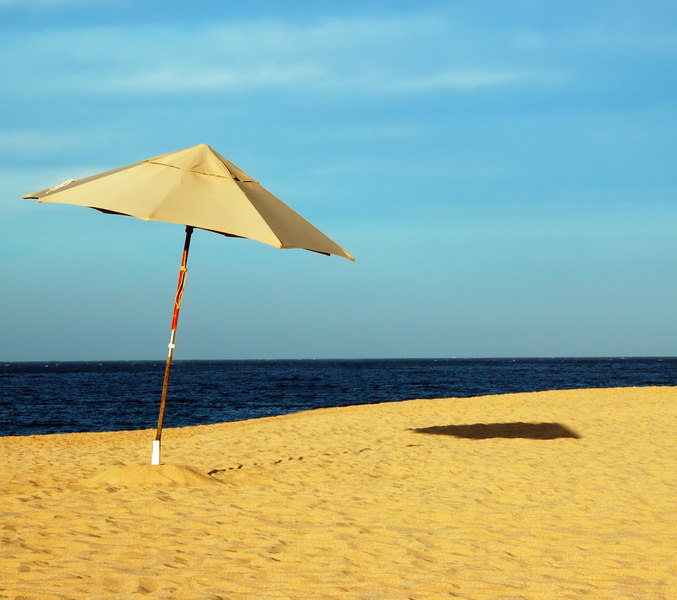 Beach Umbrella Casting a Shadow on a beach with brilliant blue ocean and sky in the background.