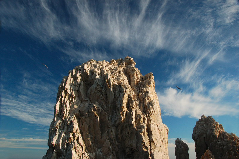 Rock formation at sunset with circling seagulls and wispy cloudsl