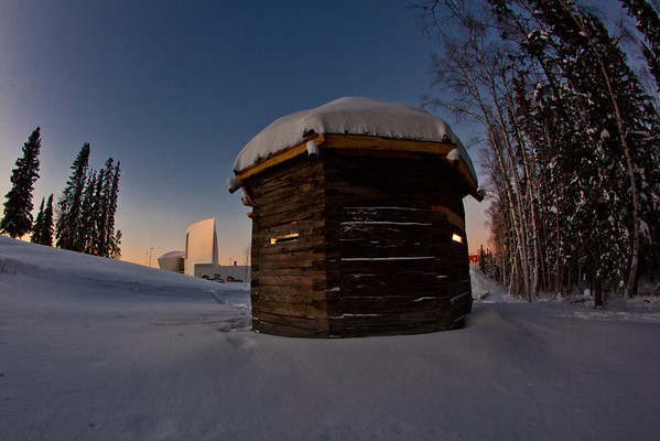 """The 1841 Russian blockhouse stands at first light on its new foundation near the University of Alaska Museum of the North. It was the first structure built by the Russian-American Company at Kolmakovsky Redoubt near Aniak. It is one of the oldest Russian-era structures in Alaska. In 1929, the blockhouse was disassembled and moved to Fairbanks where last summer a preservation team completed work on reattaching an updated roof outfitted with tundra sod and tamarack poles.  <div class=""""ss-paypal-button"""">Filename: CAM-12-3277-55.jpg</div><div class=""""ss-paypal-button-end"""" style=""""""""></div>"""