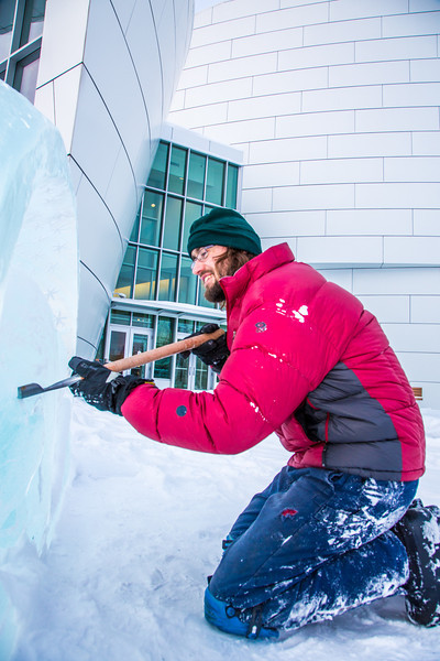 """Ronald Daanen, a research assistant professor with UAF's Institute of Northern Engineering, puts some finishing touches on an ice carving of a hibernating bear in front of the University of Alaska Museum of the North Monday afternoon.  <div class=""""ss-paypal-button"""">Filename: CAM-13-3701-14.jpg</div><div class=""""ss-paypal-button-end"""" style=""""""""></div>"""
