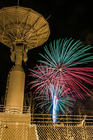 Fireworks illuminate the Alaska Satellite Facility's 11-meter antenna on West Ridge during the annual New Year's Eve Sparktacular.  Filename: CAM-13-4028-50.jpg
