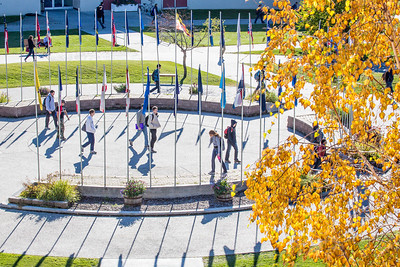 Students walk through the circle of flags in Cornerstone Plaza on the Fairbanks campus.  Filename: CAM-12-3541-55.jpg