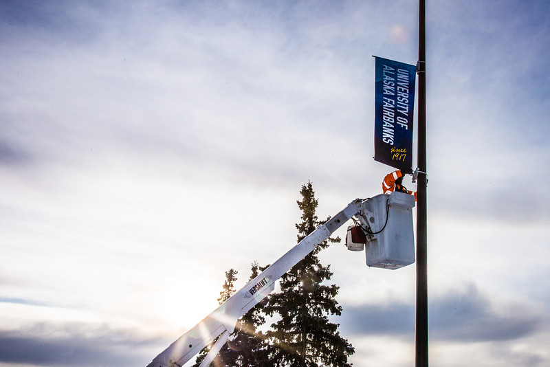 "A crew from UAF's Facilities Services monts new banners at various locations on the Fairbanks campus.  <div class=""ss-paypal-button"">Filename: CAM-13-3722-13.jpg</div><div class=""ss-paypal-button-end"" style=""""></div>"